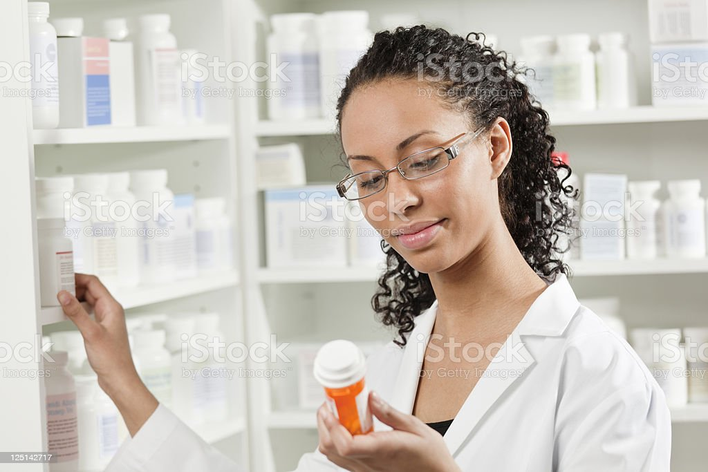 Young Black Woman Pharmacist Working with Prescription Medication in Pharmacy royalty-free stock photo
