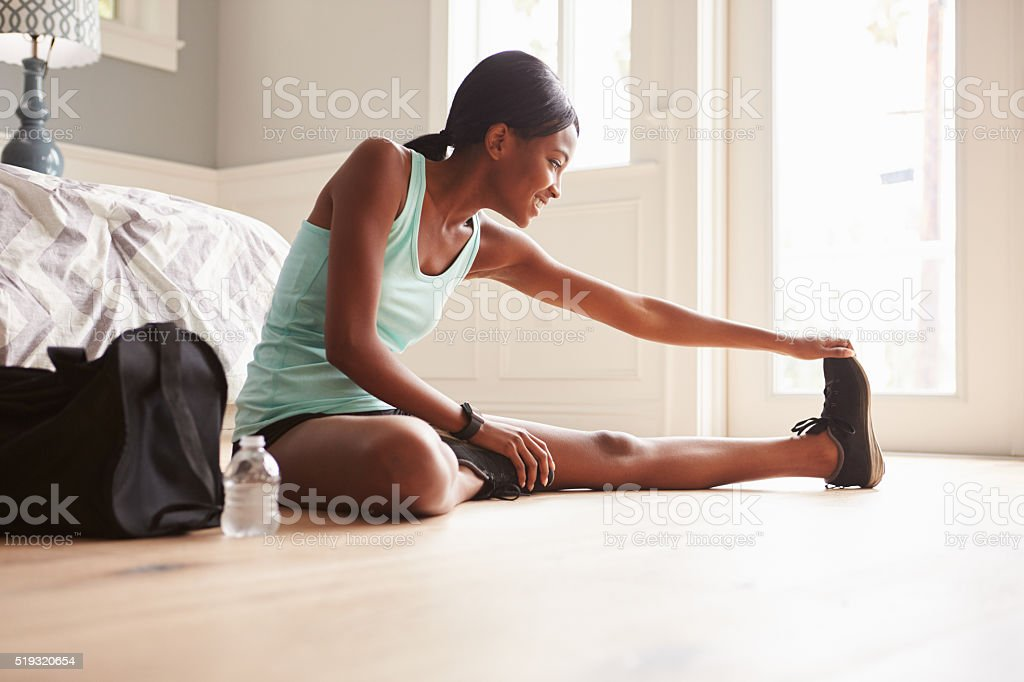 Young black woman sitting on the floor at home stretching stock photo