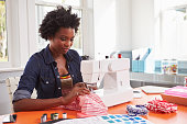 Young black woman stitching fabric using a sewing machine