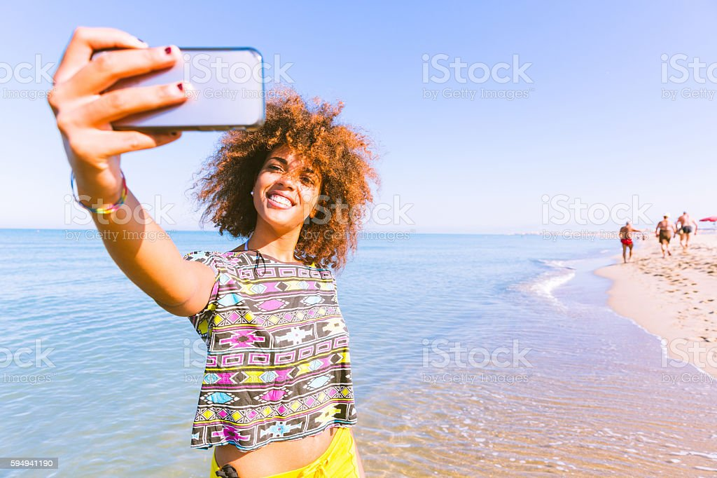 Young black woman taking a selfie at beach stock photo