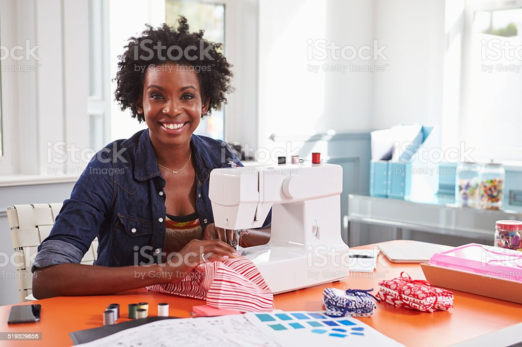 Young black woman using a sewing machine looking to camera stock photo