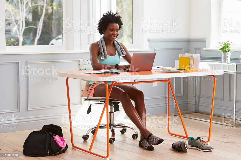Young black woman using computer at home after exercising stock photo