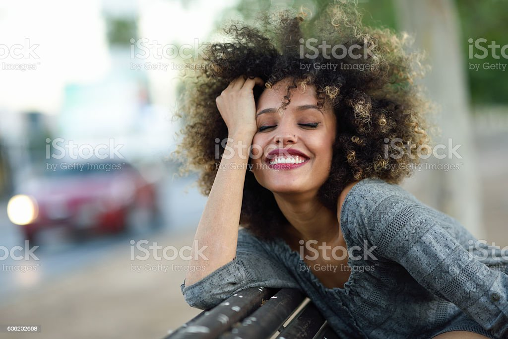 Young black woman with afro hairstyle smiling in urban backgroun stock photo