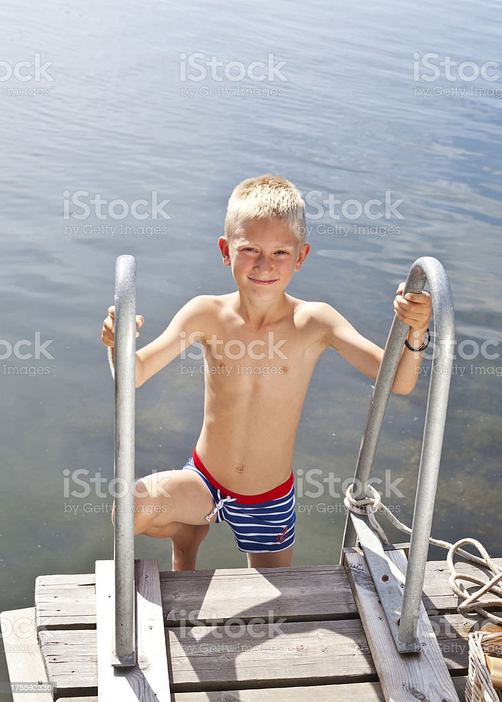 Young blond boy climbing up after swim in the sea. royalty-free stock photo