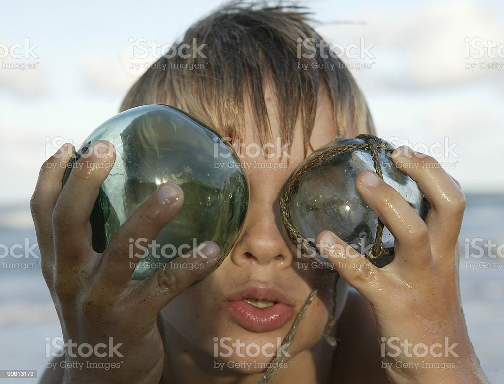 Young blond boy with glass ball acting goofy royalty-free stock photo
