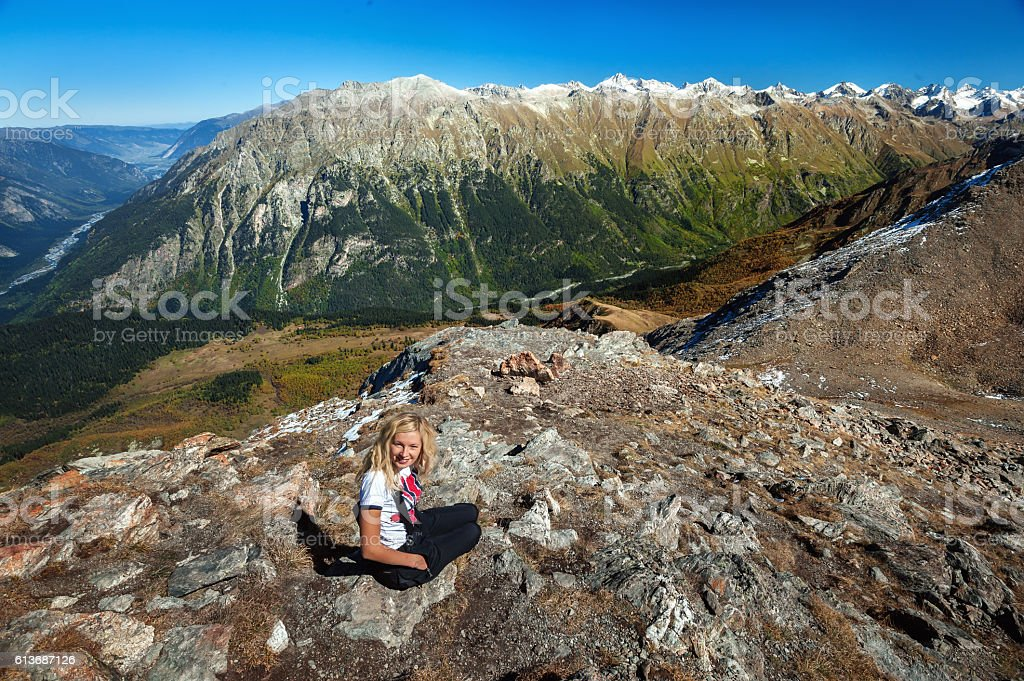 Young blond caucasian woman in the Caucasus mountains, stock photo