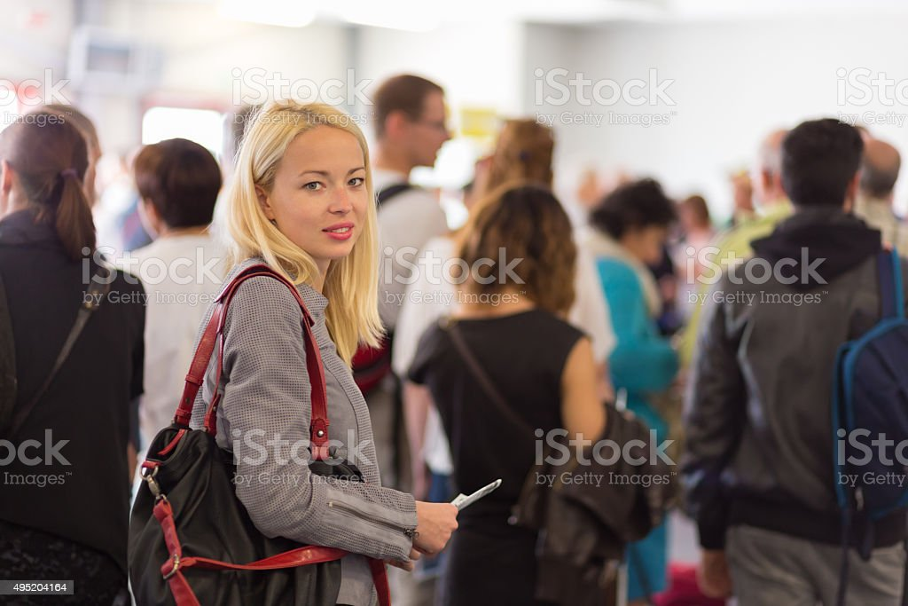 Young blond caucsian woman waiting in line. stock photo