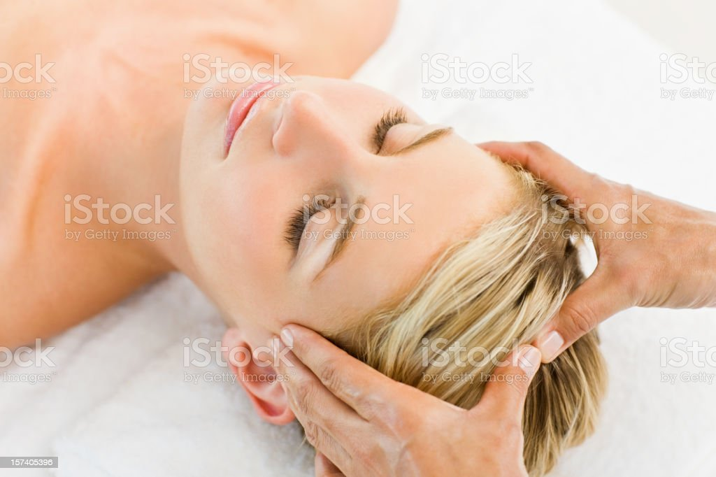 Young blond female having massage at spa stock photo