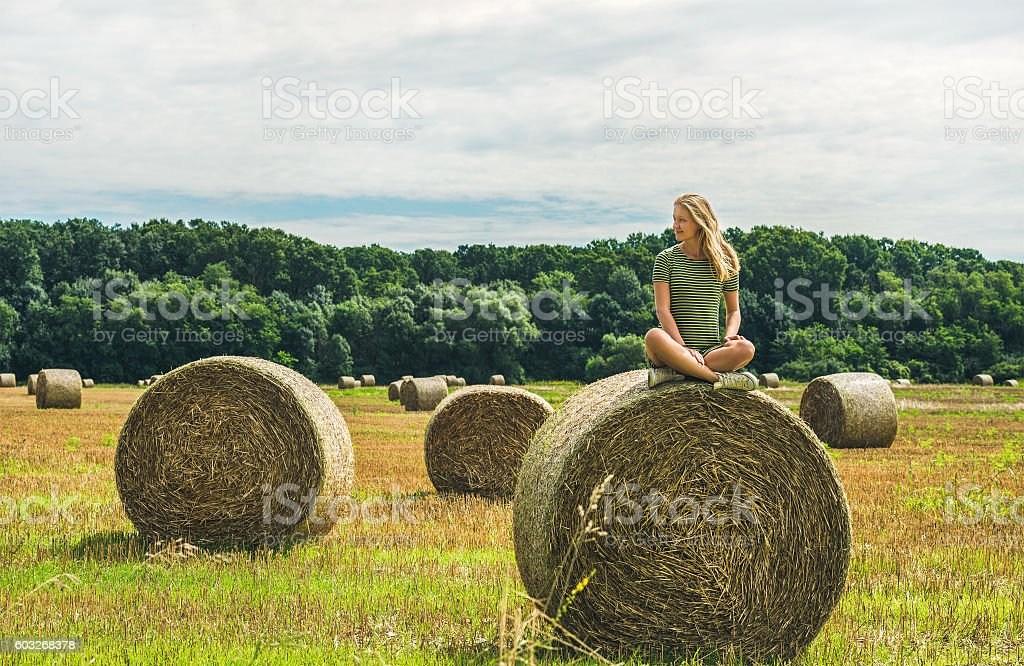 Young blond girl sitting on haystack and smiling, Hungary stock photo