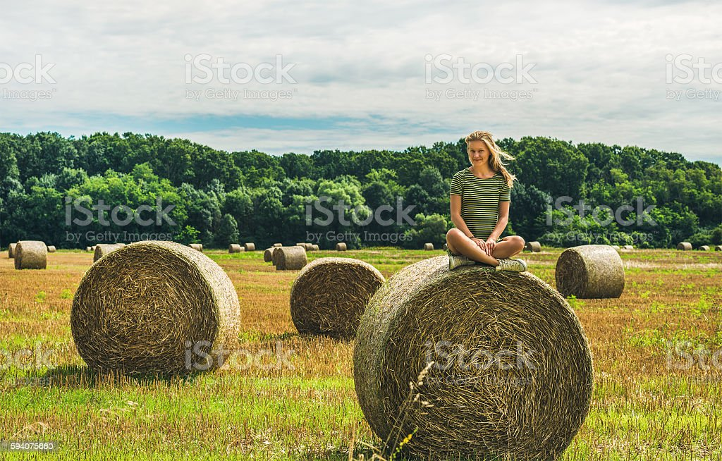 Young blond lady sitting on haystack and smiling, Hungary stock photo