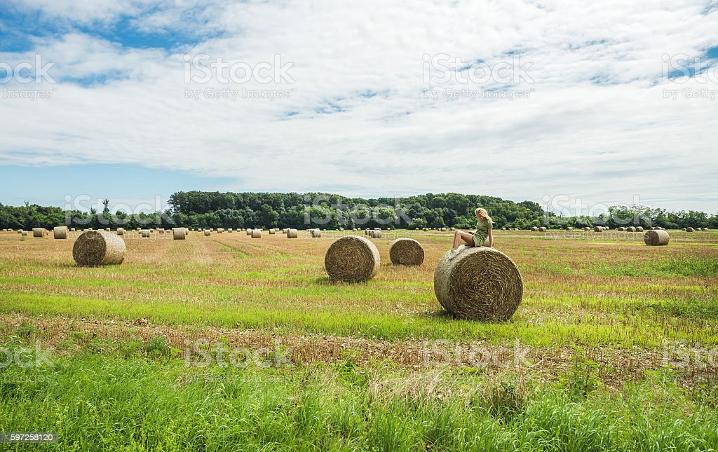 Young blond lady sitting on haystack, Hungary stock photo