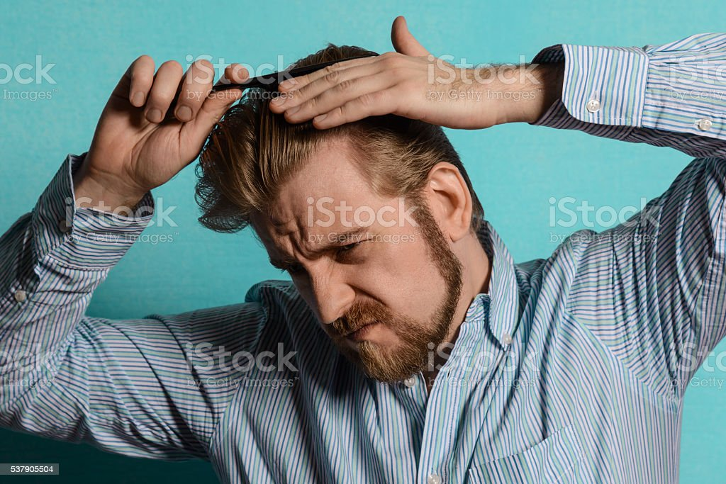 young blond man in striped shirt comb his hair stock photo