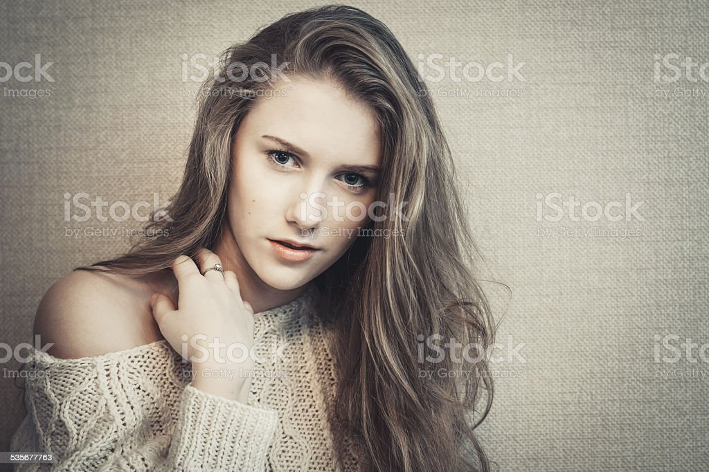 Young blond model looking at camera with questioning glance stock photo