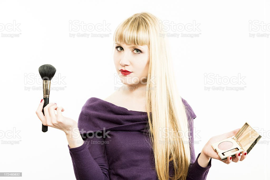 Young blond woman applying blusher royalty-free stock photo