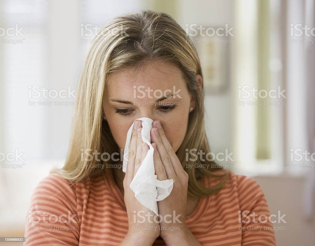 Young blond woman blowing her nose into a tissue stock photo