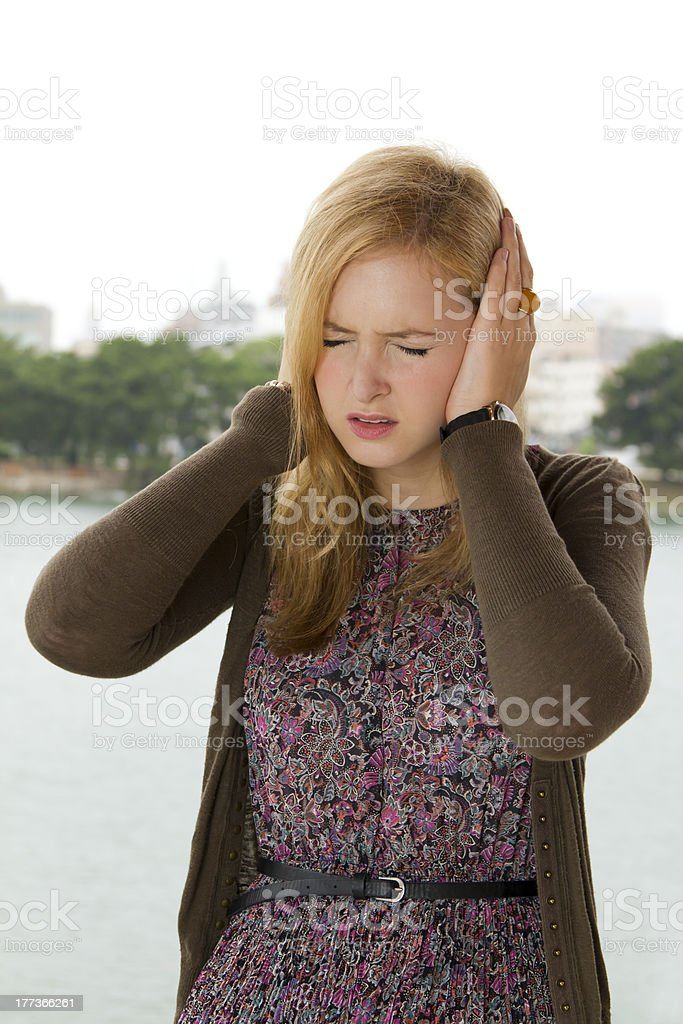 Young Blond Woman Covering Her Ears stock photo