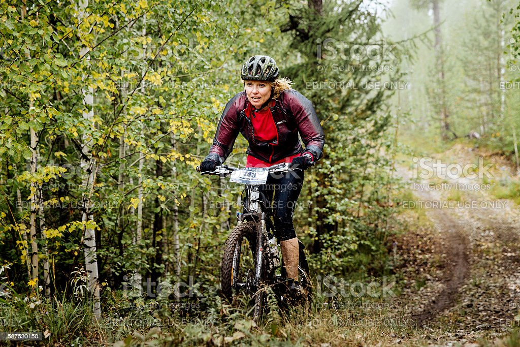 young blond woman cyclist rides through forest royalty-free 스톡 사진