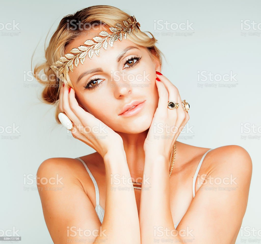 young blond woman dressed like ancient greek godess, gold jewelry stock photo