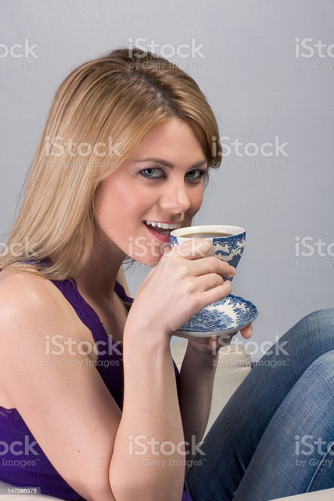 Young blond woman drinking her morning coffee stock photo