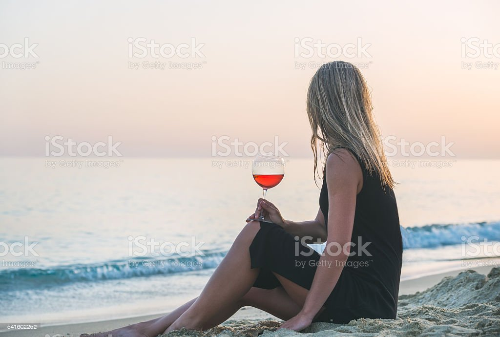 Young blond woman enjoying glass of rose wine on beach stock photo