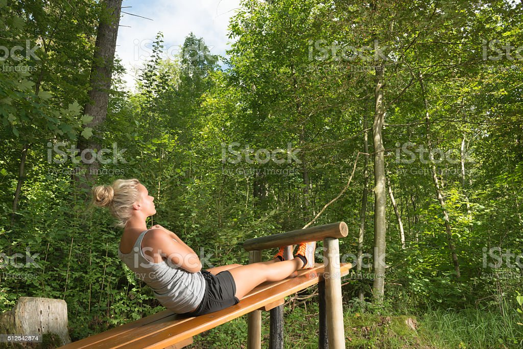 Young blond woman exercising outside her belly stock photo