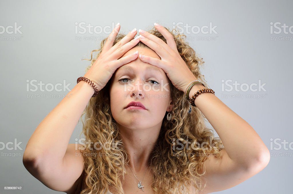 young blond woman holding her head stock photo