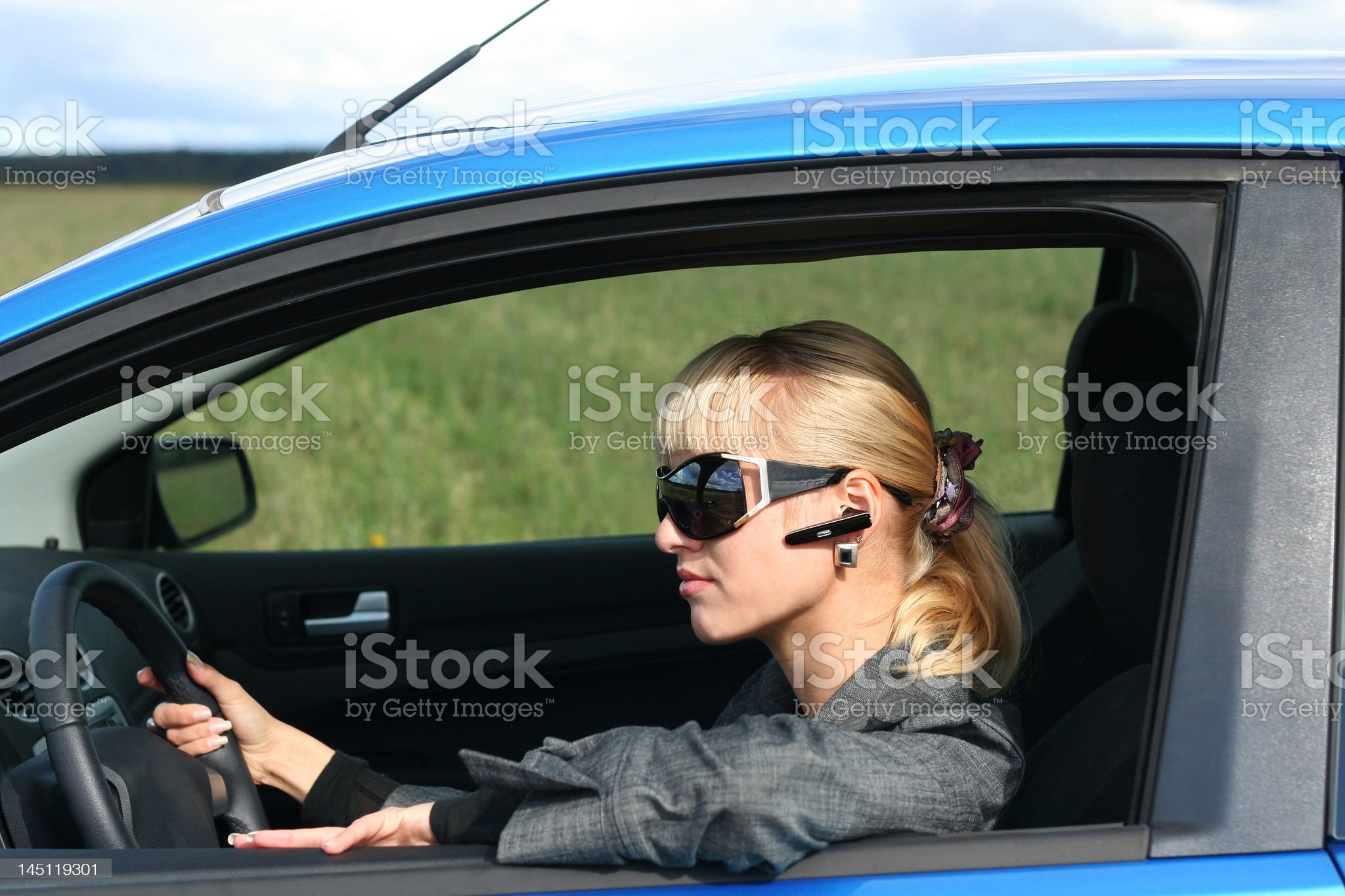 young blond woman in a blue car royalty-free stock photo