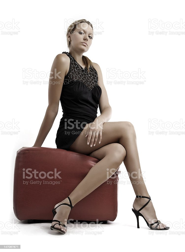 Young blond woman in black dress sitting on pouffe royalty-free stock photo
