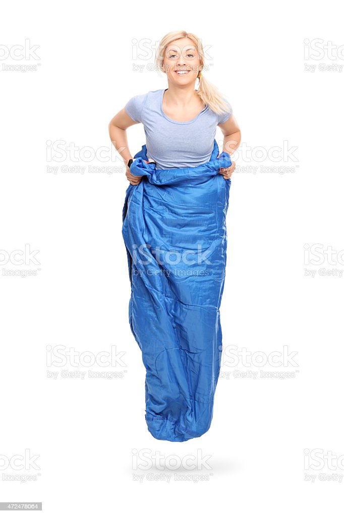 Young blond woman jumping in a blue sack stock photo