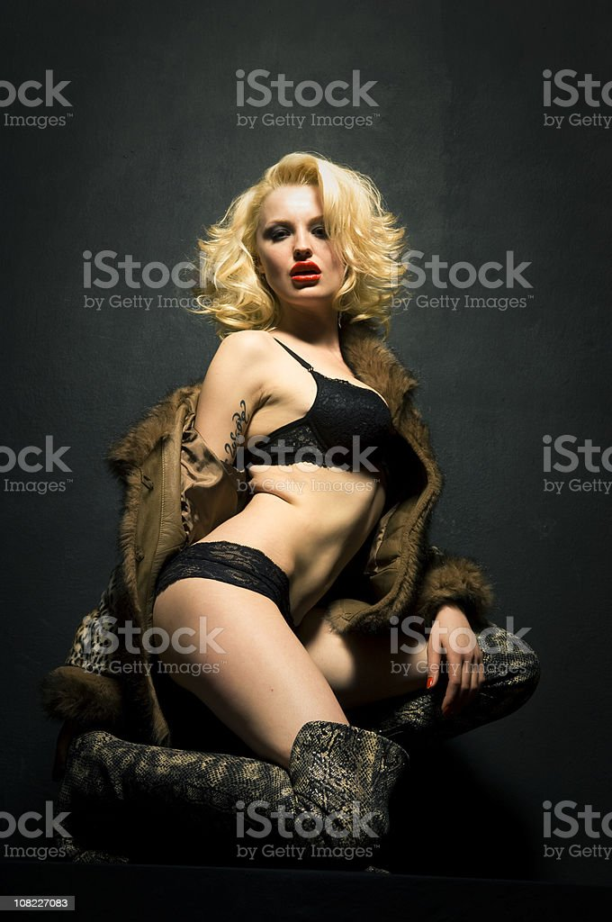 Young Blond Woman Kneeling and Posing Wearing Lingerie stock photo