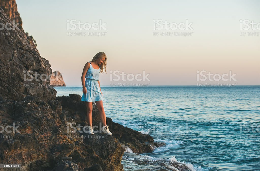 Young blond woman looking at still water, Alanya, Turkey stock photo