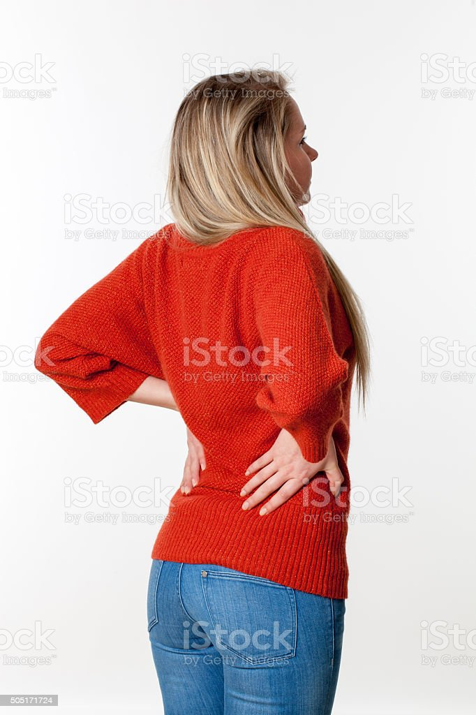 young blond woman massaging her lower back vertebrae stock photo