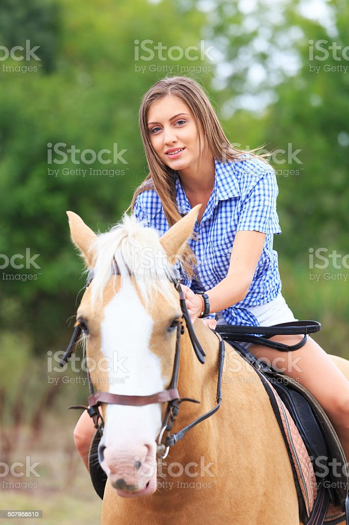 Young blond woman on the horse stock photo