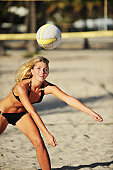 Young Blond Woman playing beach volleyball