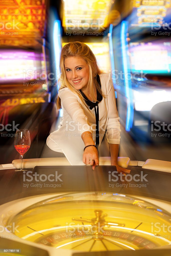 Young blond woman playing roulette in casino and winning stock photo