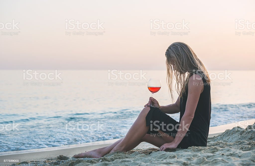 Young blond woman relaxing with glass of rose wine on stock photo