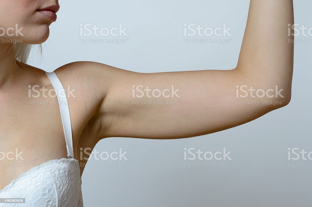 Young blond woman showing flabby arm stock photo
