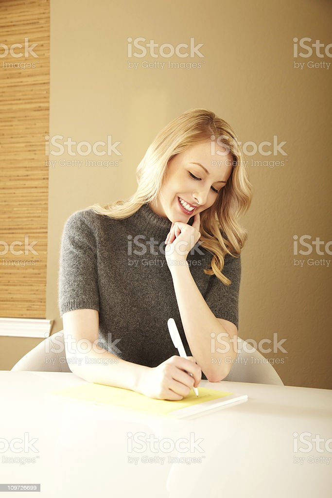 Young Blond Woman Sitting at Table and Writing Notes royalty-free stock photo