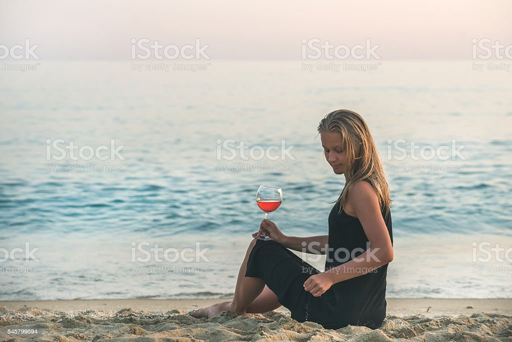 Young blond woman sitting with glass of rose wine on stock photo