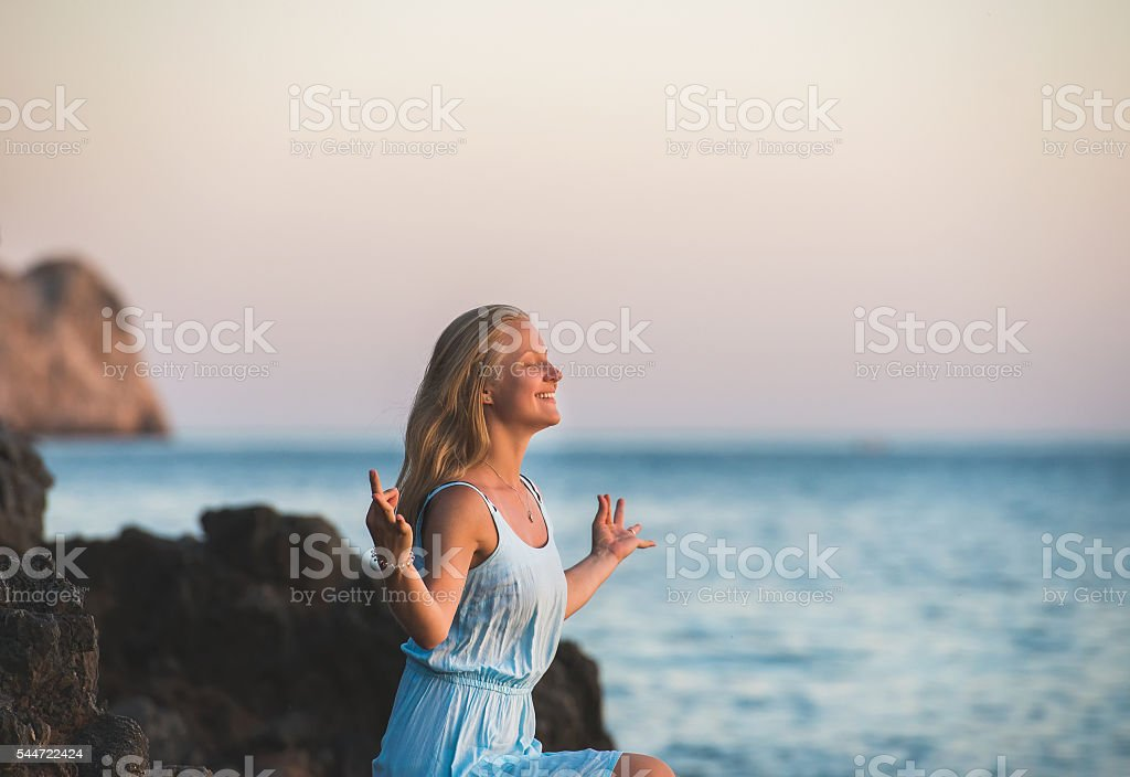 Young blond woman tourist in blue dress relaxing, meditating and stock photo