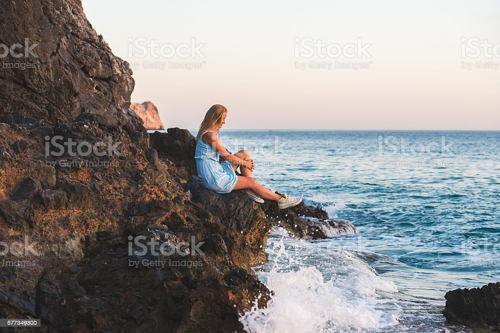 Young blond woman tourist in blue dress relaxing on stone stock photo