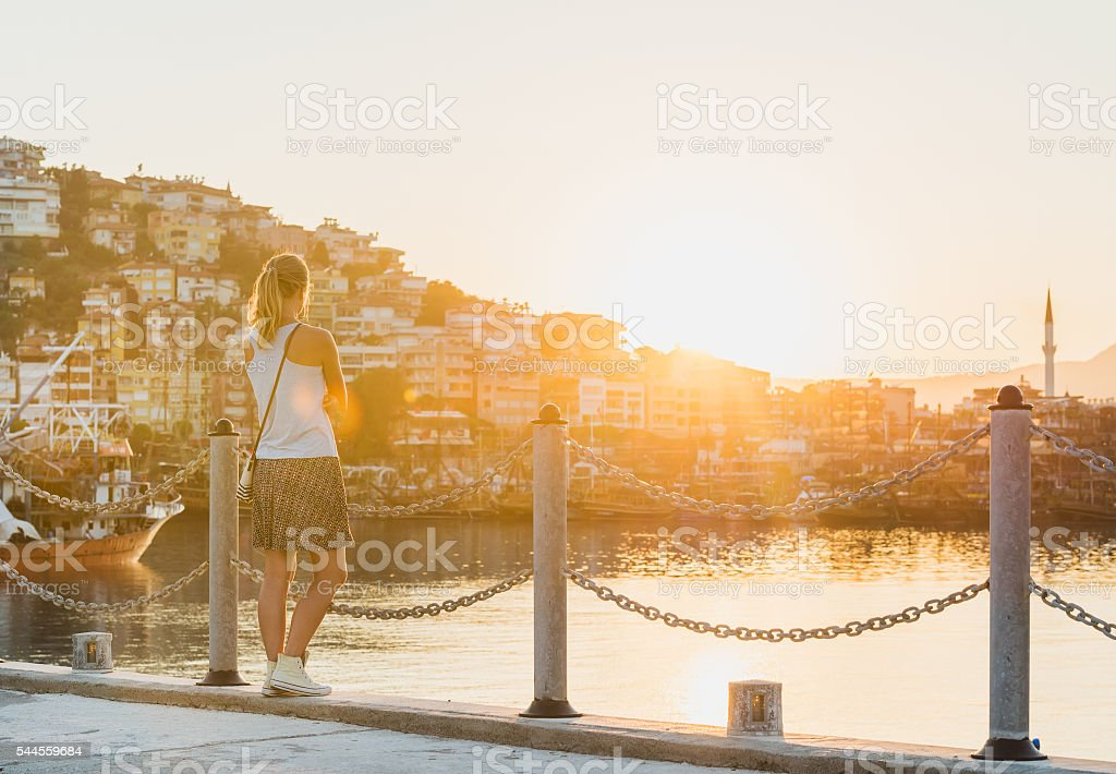 Young blond woman watching sunset stock photo