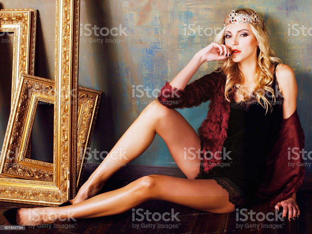 young blond woman wearing crown in fairy luxury interior with stock photo