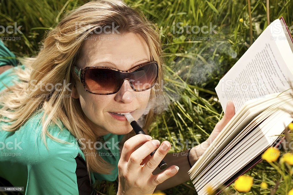 young blond woman with electric cigarette is reading a book royalty-free stock photo