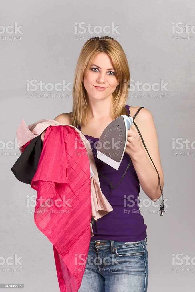 Young blond woman with iron and pile of clothes royalty-free stock photo