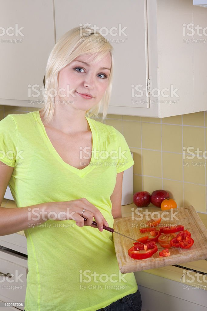 Young blond woman with vegetables on kitchen royalty-free stock photo