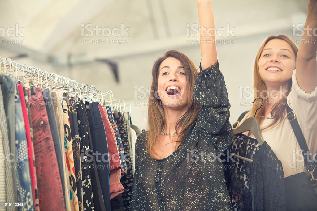 Young blonde and brown friends enjoy in secondhand clothing shop stock photo