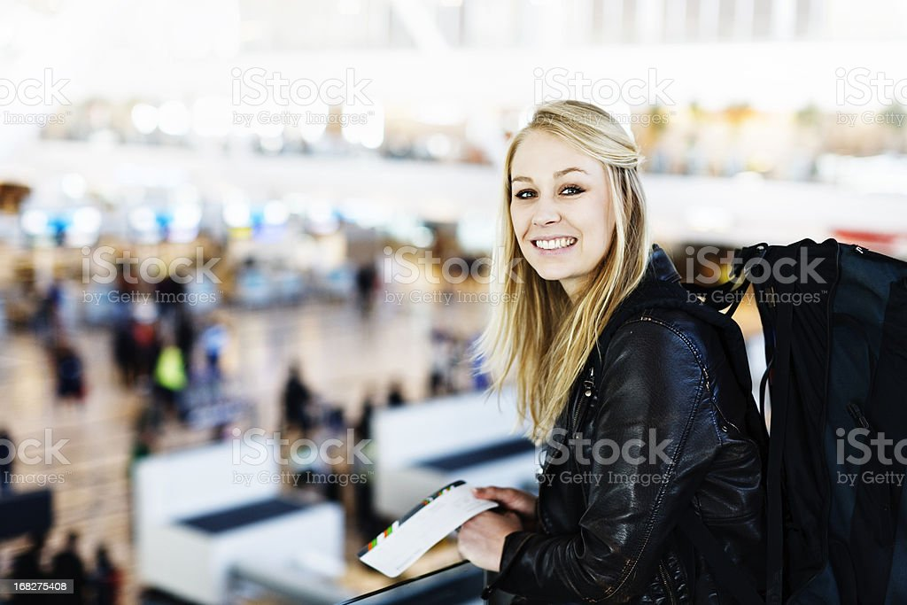 Young blonde backpacker with boarding pass looking over airport check-in stock photo