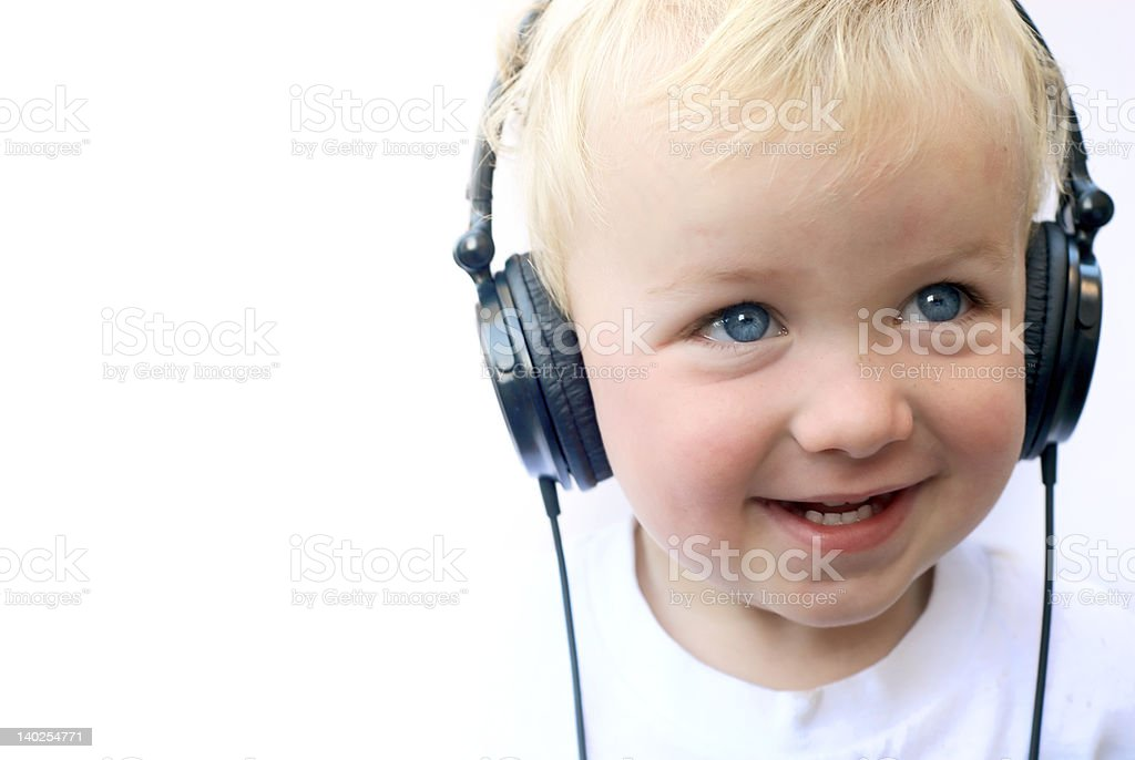 Young blonde boy smiling with headphones on stock photo