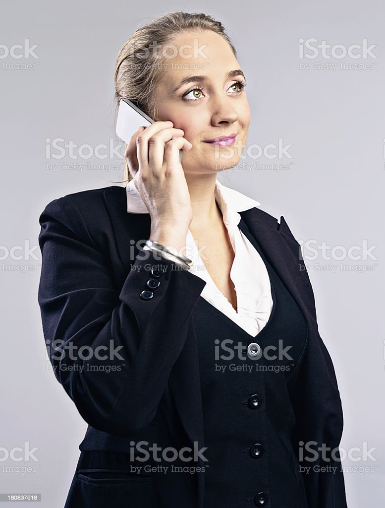 Young blonde businesswoman listens to mobile phone, smiling stock photo